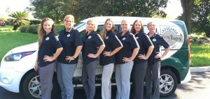 The Villages Insurance team standing in front of company vehicle parked in front of manicured Florida landscaping