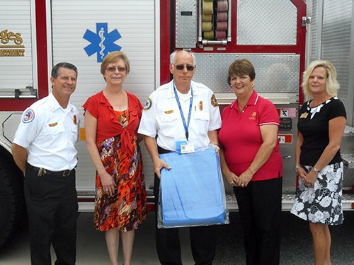 The Villages Insurance Partners team members stand in front of an ambulance alongside of EMTs
