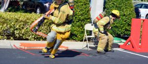 firemen in training in a parking lot, one grabs a firehouse while another springs into action