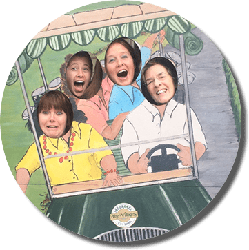 group poses in a cut out picture of a golf cart