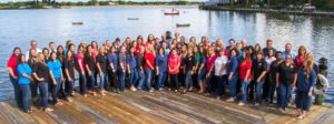 The Villages Insurance Team grouped together posing on dock in front of water