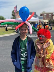 Teenage boy with balloon octopus on head standing next to clown