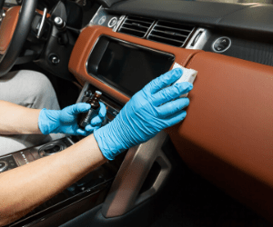 Golved hands cleaning inside of car